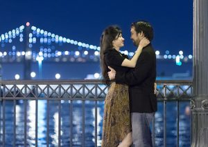 Nighttime engagement photos with the Bay Bridge as backdrop