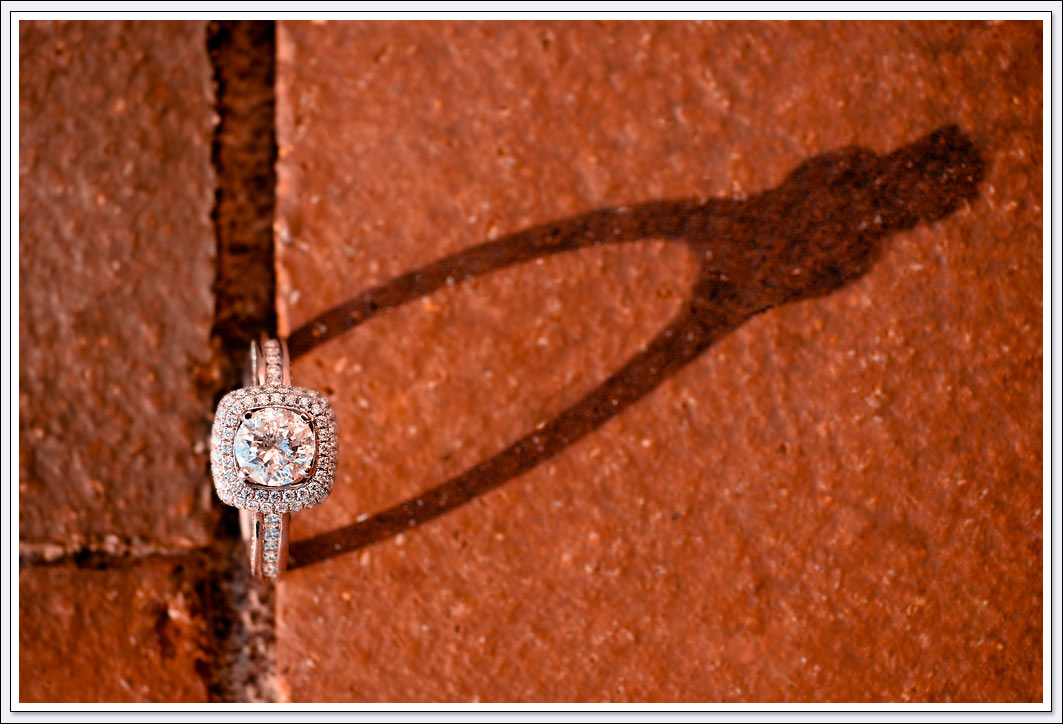 The engagement ring casts a shadow over the red bricks