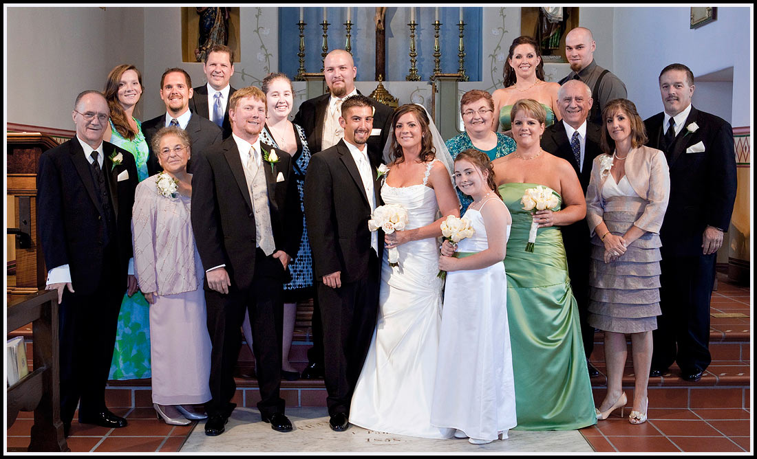 Family members and the bridal party take a group photo on the alter steps at the San Carlos Cathedral church in Monterey California