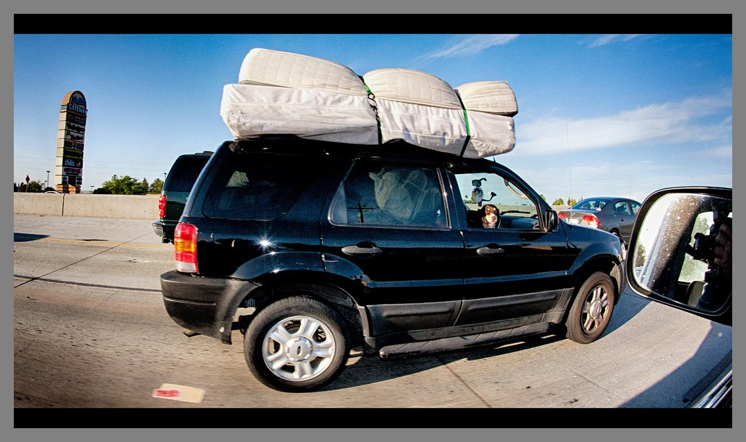 Black SUV with mattresses tied to roof - Highway 4 - Brentwood, CA