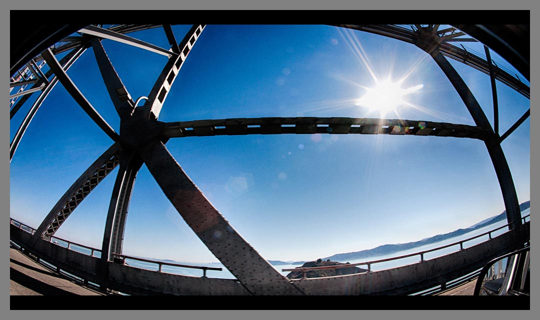 The sun shines through support beams of the Richmond - San Rafael bridge. Photographed with a fisheye lens and Canon full frame camera.