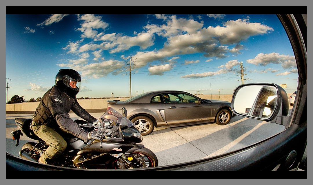 The use of fill flash on the high shutter speed image illuminates the face of the motorcycle drive - Highway 4 - California