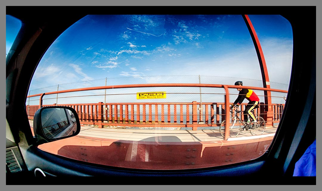 Bicycle rider on the Golden Gate bridge photographed with fisheye lens and then HDR processed.