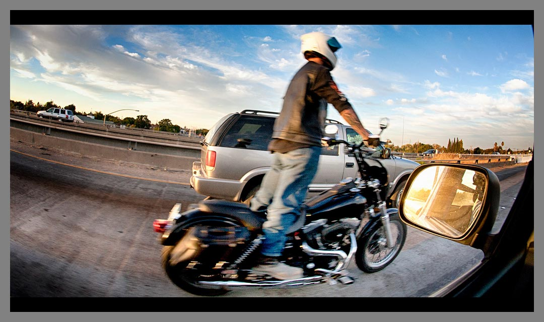 Motorcycle rider standing up while riding through the slow traffic of Highway 4 in Pittsburg, CA.