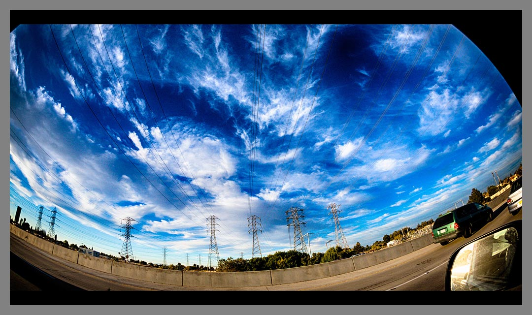 Electric transmission towers and fluffy blue sky along Highway 4.