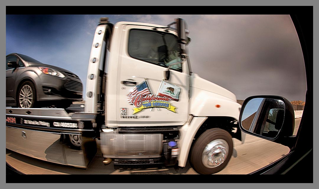 The white California Tow Service truck driving along Highway 4.