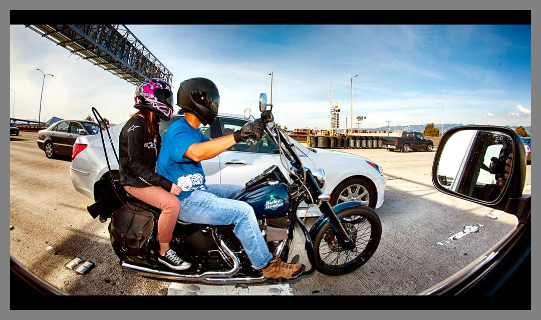 Motorcycle with two people aboard drives Eastbound on Interstate 80 just off the San Francisco - Oakland Bay Bridge.