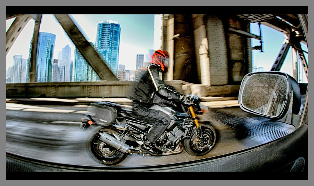 Motorcycle cruising East bound on the Lower Deck of the San Francisco - Oakland Bay bridge before Treasure Island with San Francisco skyline in background.