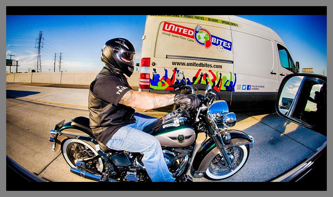 Motorcycle passing by United Bites van.